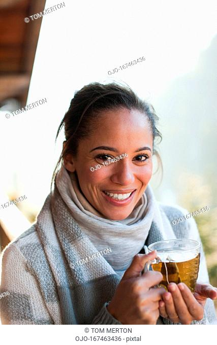 Portrait of smiling woman drinking tea