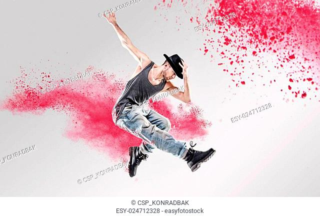 Portrait of a dancer excercising among a colorful dust