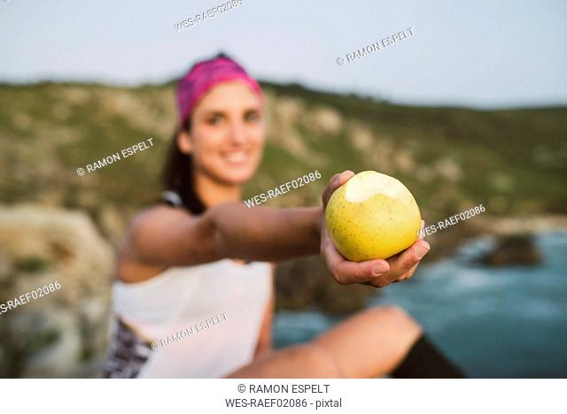 Sportive woman sitting on rocks, holding apple, focus on foreground