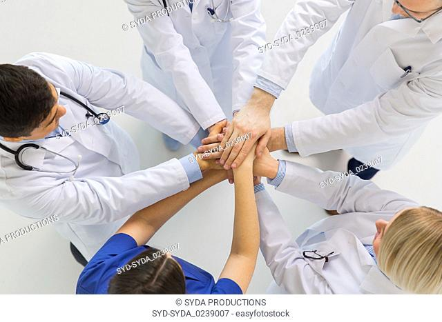 group of doctors with hands together at hospital