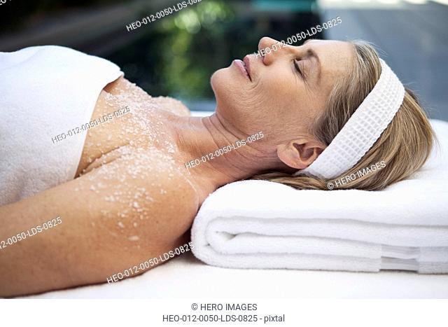 middle aged woman having salt scrub treatment