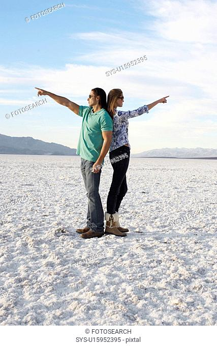 Couple standing back to back and pointing to opposite directions in desert