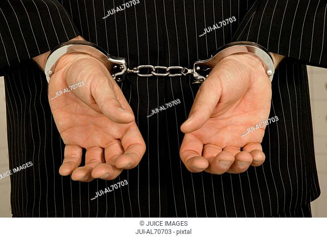 Rear view of thief in handcuffs