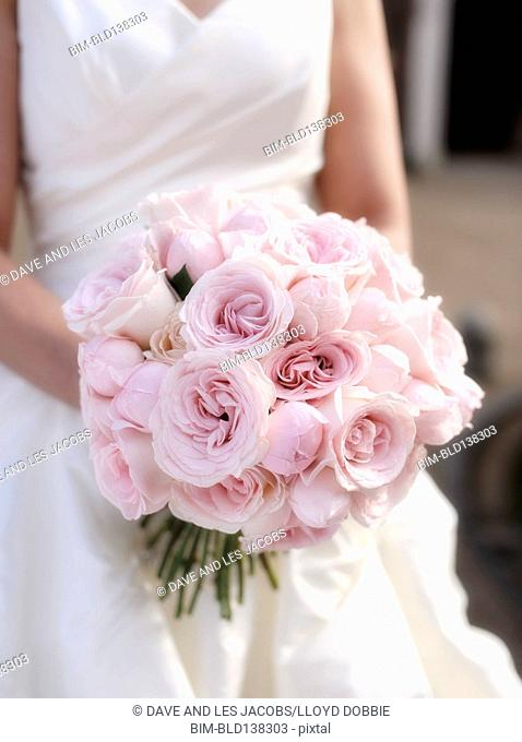 Close up of Hispanic bride holding bouquet of roses