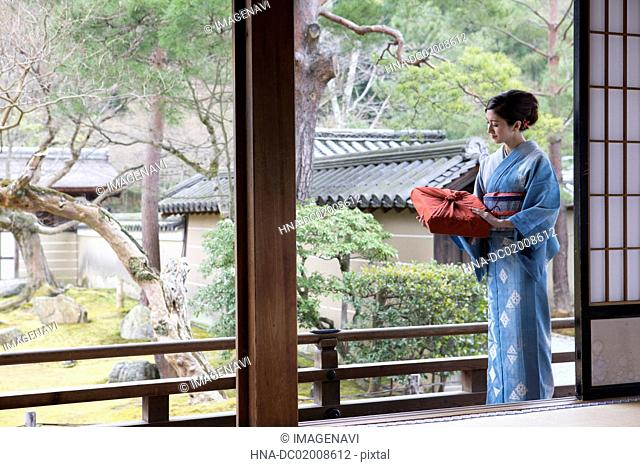 Young Japanese woman in kimono with parcel
