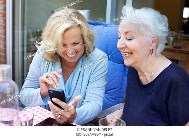 Two women, sitting outdoors, looking at smartphone