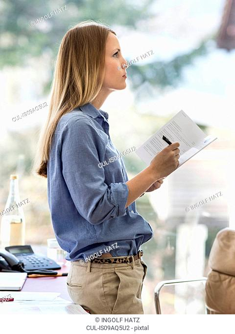 Young businesswoman writing notes whilst leaning against home desk