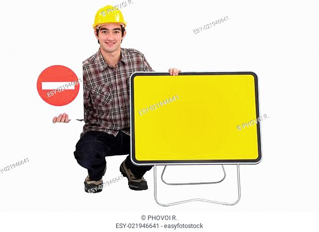 Traffic worker kneeling by road signs