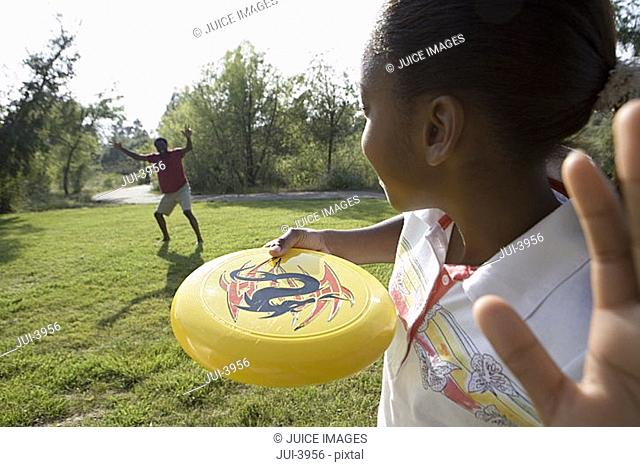 Girl 11-13 playing frisbee with father in park, smiling, close-up, rear view