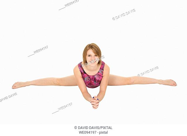 Caucasian teenage girl in gymnastic poses on white background