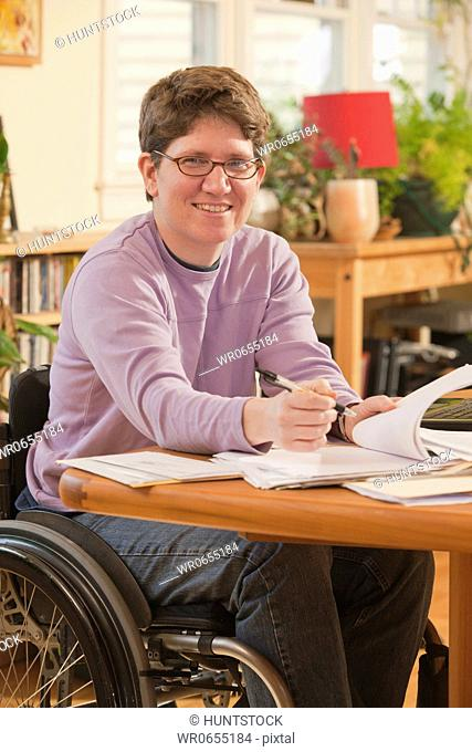 Businesswoman with multiple sclerosis in a wheelchair doing paperwork at home