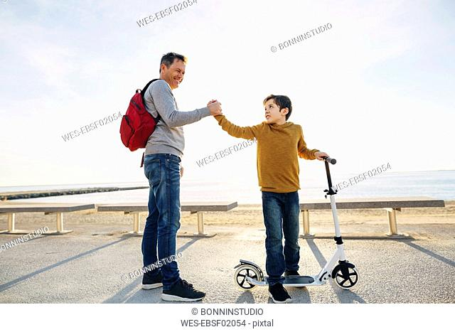 Father and son with scooter shaking hands on beach promenade at sunset