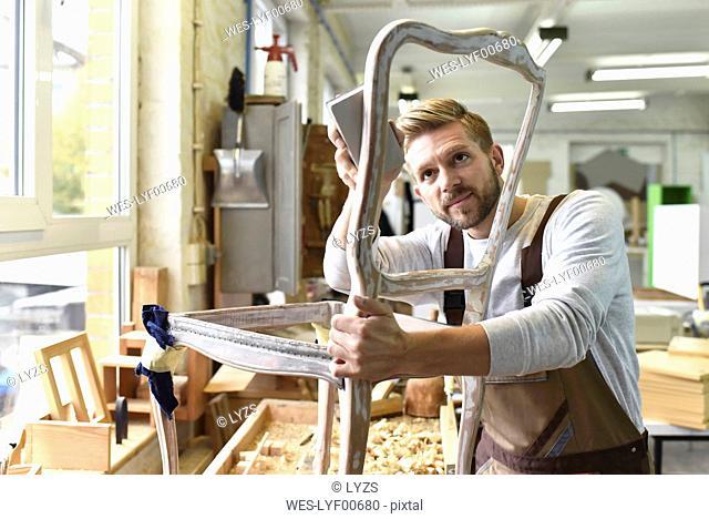 Carpenter restoring a wooden chair