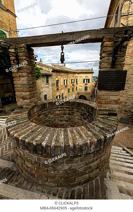 The ancient stone well among the houses of the old town of Corinaldo Province of Ancona Marche Italy Europe