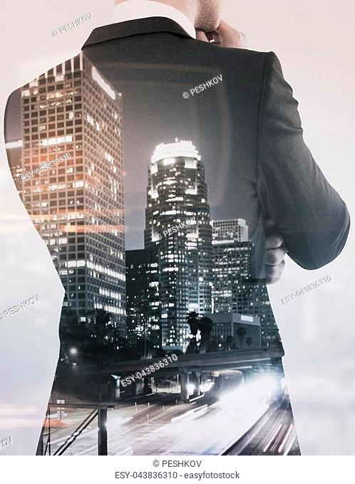 Unrecognizable thoughtful businessman on creative city background. Think concept. Double exposure