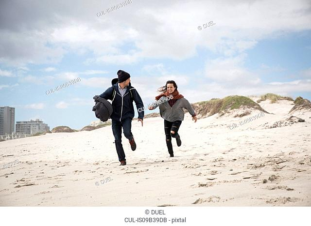 Young couple running on windswept beach, Western Cape, South Africa