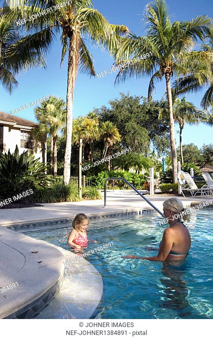Grandmother and granddaughter relaxing in swimming pool