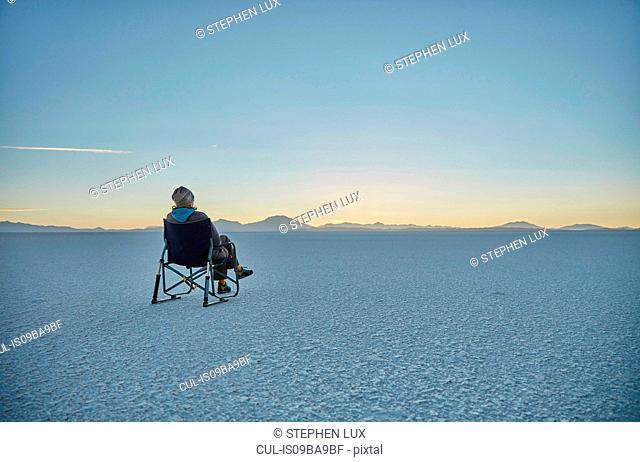 Woman sitting in camping chair, on salt flats, looking at view, Salar de Uyuni, Uyuni, Oruro, Bolivia, South America