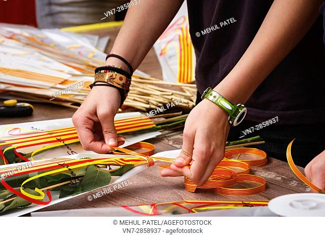 Ribbons with the Catalan colours being tied to a rose bouquet on the day Sant Jordi (April23) in Tarragona, Catalonia, Spain