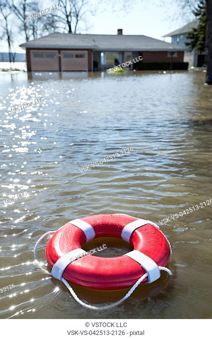 View of flooded house and lifebelt floating on water
