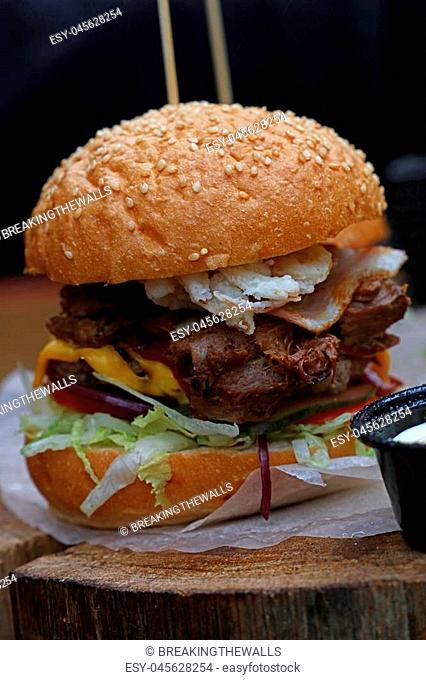 Big American burger with pulled pork meat, onion rings, cheese and salad in sesame bun on paper parchment over natural wooden cut, close up, low angle view