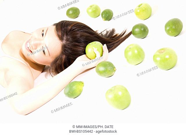 A pretty young asian woman poses with green fruits