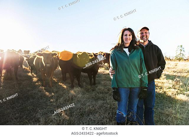 Farmer couple with grass fed cattle on their farm; Grannis, Arkansas, United States of America