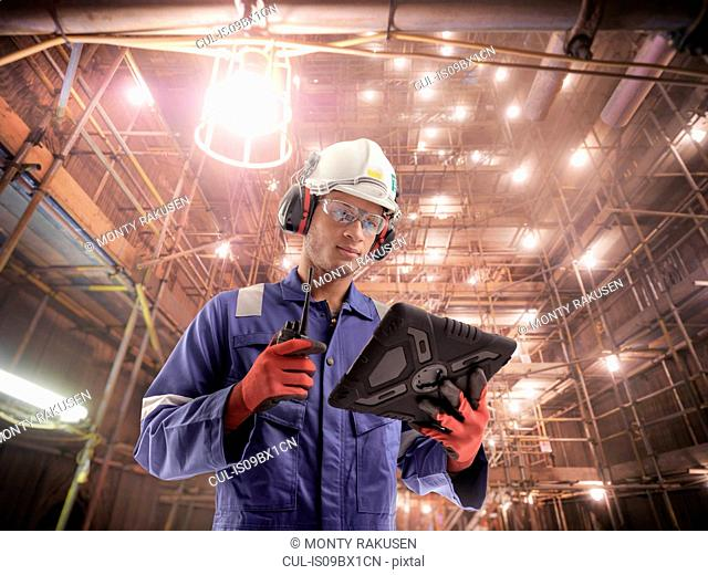 Composite image of engineer inside power station during outage using digital tablet