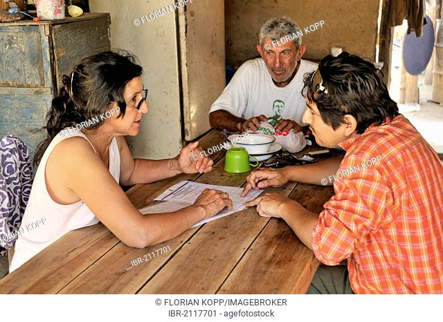 Land grabbing, consultation, development worker, right, consulting smallholding couple on legal issues, if the farmers fail to prove their claim to the land...