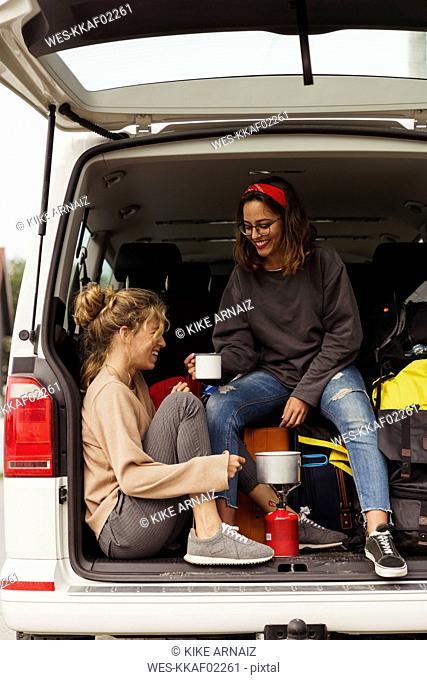 Friends sitting in a camper, taking a break, drinking coffee