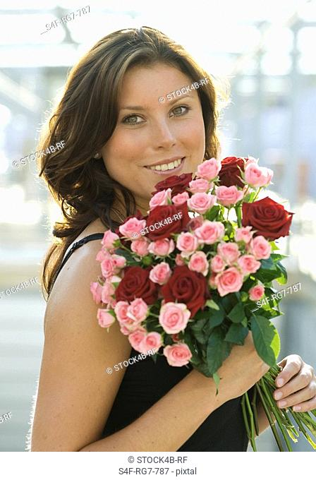 Brunette woman holding bunch of roses