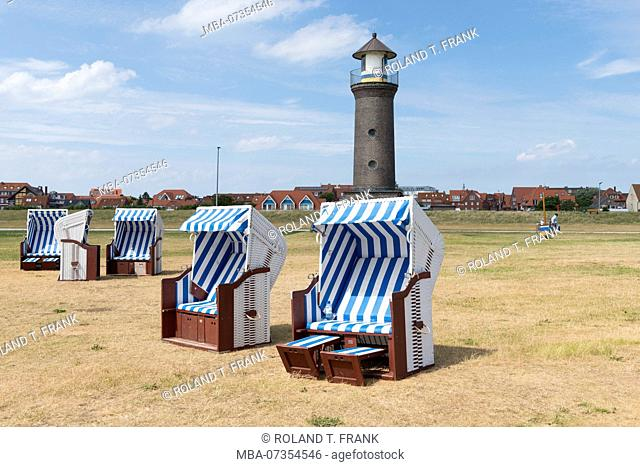 Germany, Lower Saxony, East Frisia, Juist, the Memmertfeuer / lighthouse at the harbor with beach chairs in the foreground