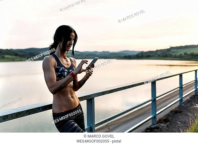 Female athlete checking smart phone leaning on railing