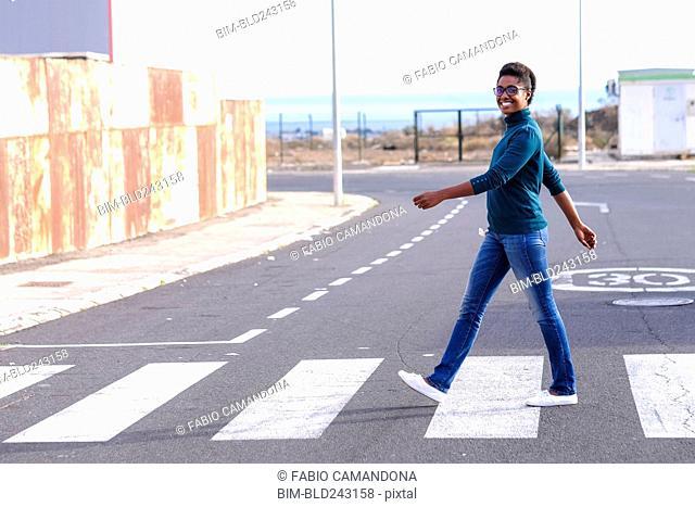 Smiling African American woman walking in crosswalk