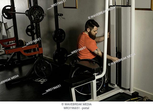 Handicapped man on wheelchair increasing weight of pulldown exercise
