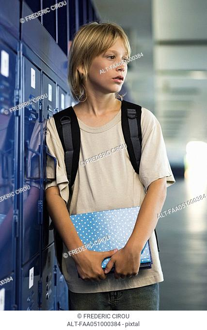 Junior high student leaning against locker in school corridor