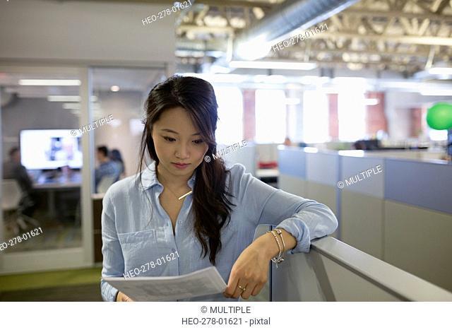 Businesswoman reviewing paperwork in office corridor