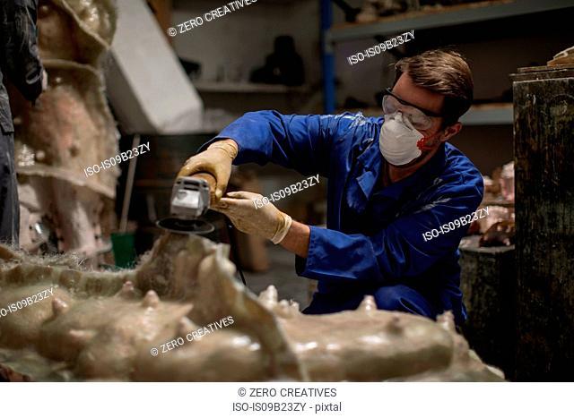 Sculptor in artists' studio sanding sculpture