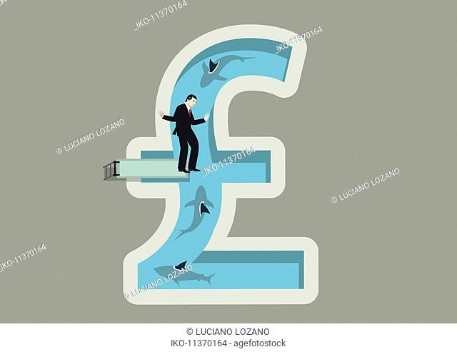 Businessman balancing on diving board above shark infested British pound shaped swimming pool