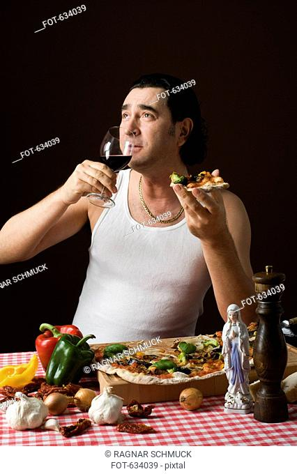 Stereotypical italian man holding a wine glass and eating pizza