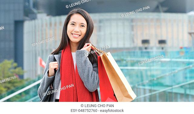 Young woman use of mobile phone in city and holding shopping bag