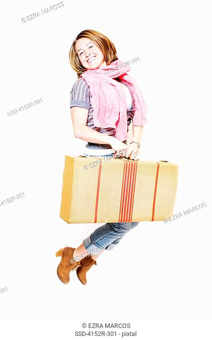 Young woman with suitcase jumping