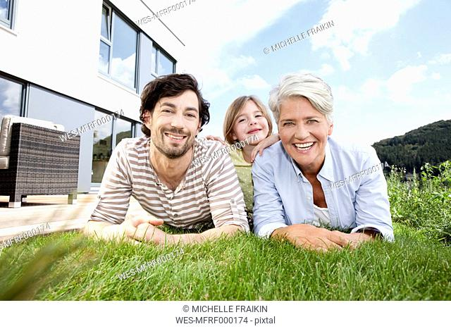 Portrait of happy grandmother, father and girl lying on lawn