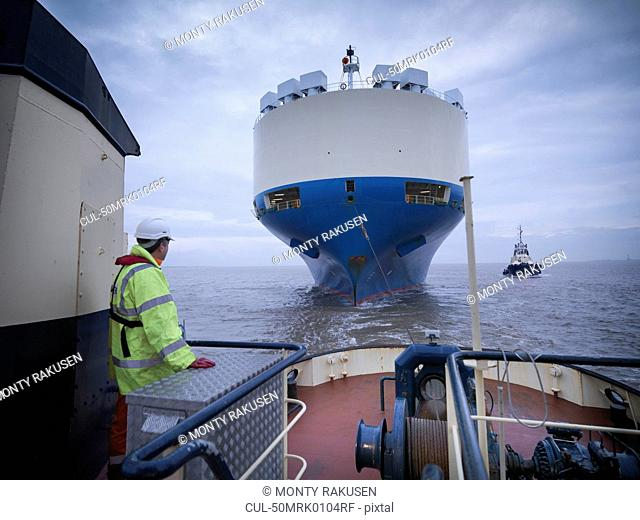 Worker standing on deck of tugboat