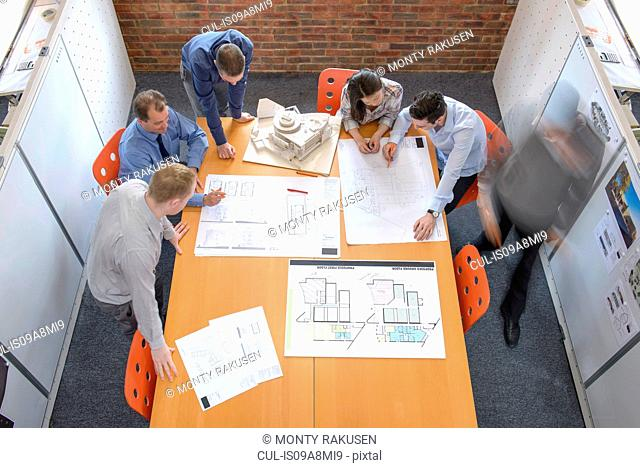 Team of architects discussing plans in meeting room, blurred motion