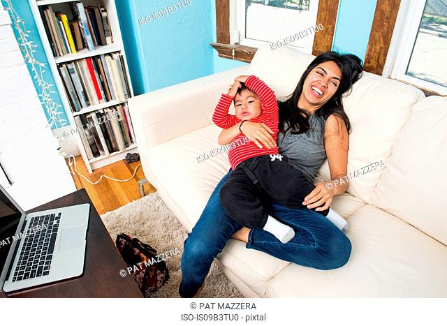 Woman with toddler son on lap laughing on sofa