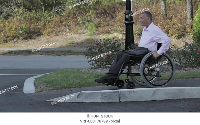 Man with spinal cord injury in a wheelchair using accessible sidewalk to street ramp and kissing wife