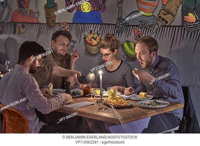 Friends enjoying dinner in restaurant Blitz, Museumsinsel, near Isartor, Munich, Germany. South-African and vegetarian food.. German ethnicity