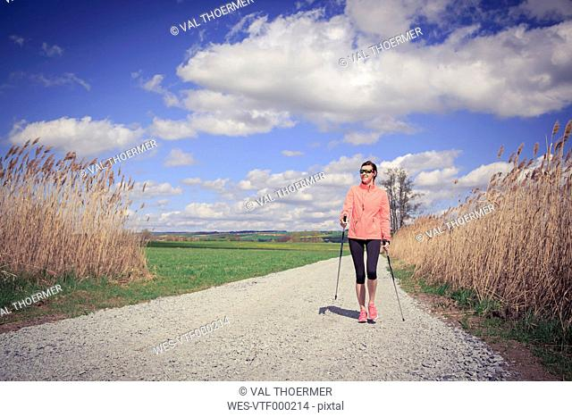 Female Nordic walker on the move through the rural landscape