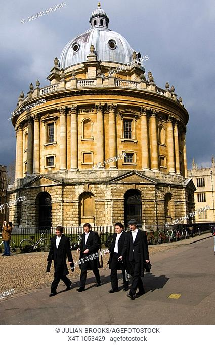 A group of students in gowns walking past the Radcliffe camera, Oxford  in the sunshine with clouds gathering behind